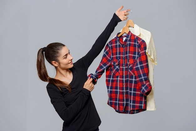 Mujer sosteniendo camisas, eligiendo qué ropa usar