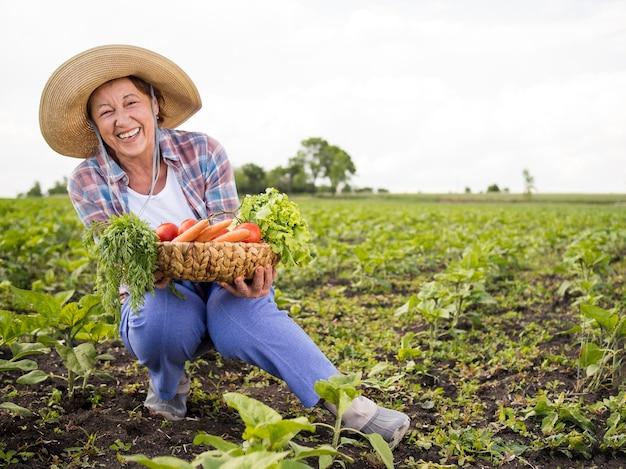 Mujer sosteniendo una canasta llena de verduras con espacio de copia