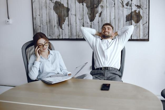 Mujer sosteniendo una carpeta. chica está hablando por teléfono. gente sentada en la mesa