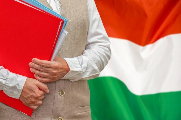 Mujer sosteniendo una carpeta roja con la bandera de hungría detrás