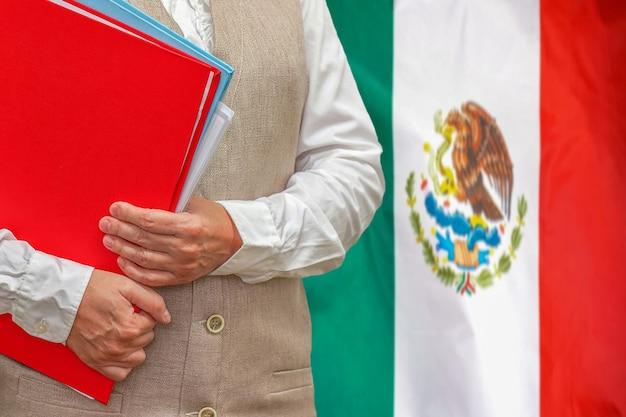 Mujer sosteniendo carpeta roja con la bandera de méxico detrás