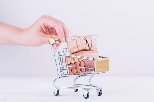 Mujer sosteniendo un carrito de supermercado con cajas de regalo