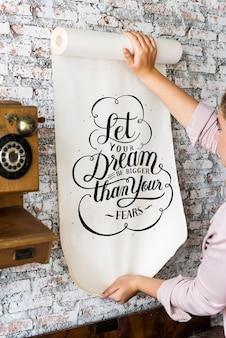 Una mujer sosteniendo un cartel con cita de motivación.