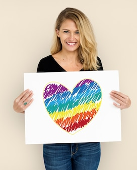 Mujer sosteniendo el cartel con el icono del corazón lgbt