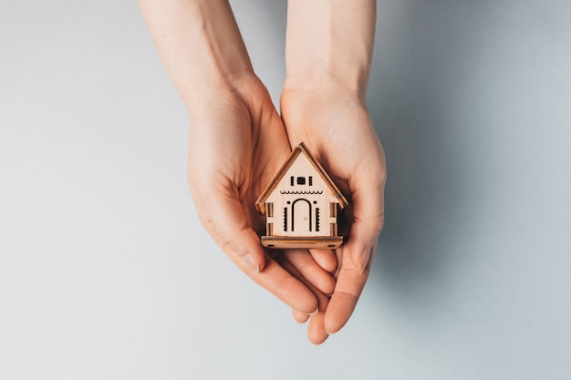 Mujer sosteniendo una casa de madera con sus manos con el sol en un espacio azul claro