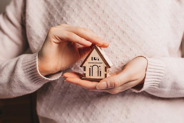 Mujer sosteniendo una casa de madera con sus manos con el sol en un espacio de color rosa claro