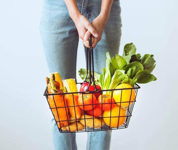 Mujer sosteniendo cesta de vegetales