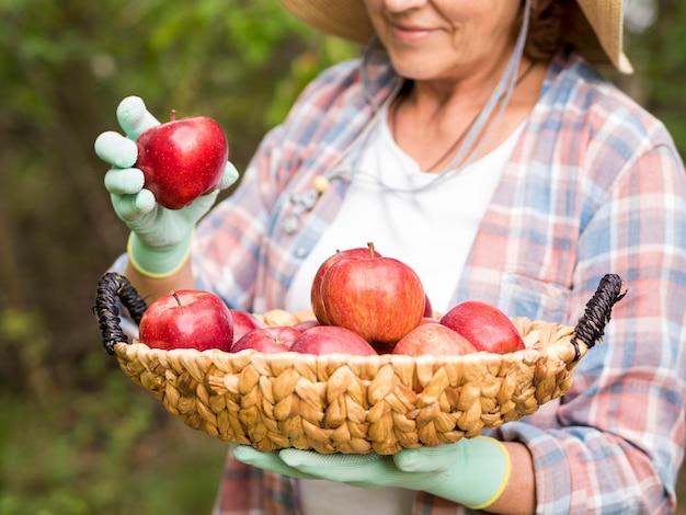Mujer sosteniendo una cesta llena de manzanas