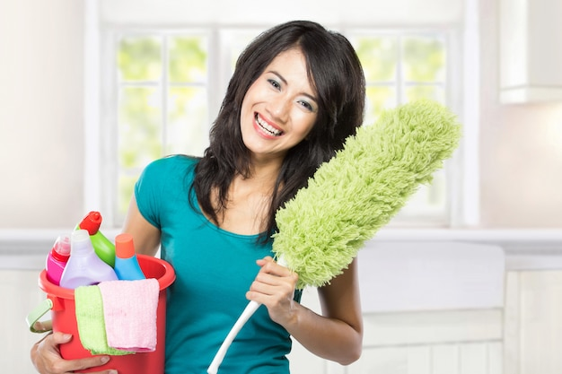 Mujer sosteniendo una cesta llena de productos de limpieza listos para hacer som