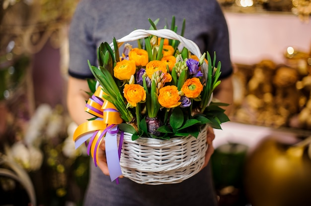 Mujer sosteniendo una cesta de mimbre con flores.
