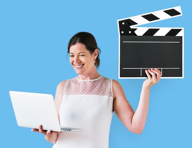 Mujer sosteniendo una chapaleta y una computadora portátil