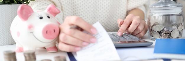 Mujer sosteniendo cheques para compras en mano y contando con calculadora closeup