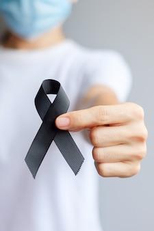 Mujer sosteniendo cinta negra para melanoma y cáncer de piel, mes de concientización sobre lesiones por vacunación, dolor y descanso en paz. concepto de salud y racista