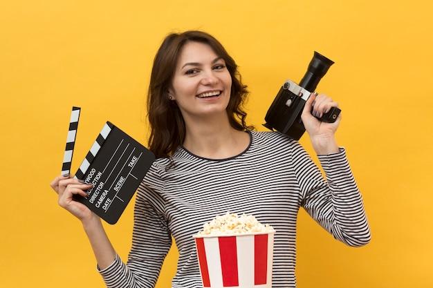 Mujer sosteniendo una claqueta y una cámara de cine