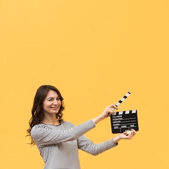 Mujer sosteniendo una claqueta con espacio de copia