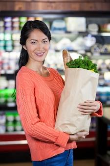 Mujer sosteniendo comestibles en bolsa de papel