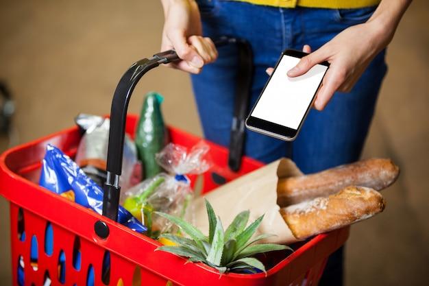 Mujer sosteniendo comestibles y teléfono móvil en supermercado