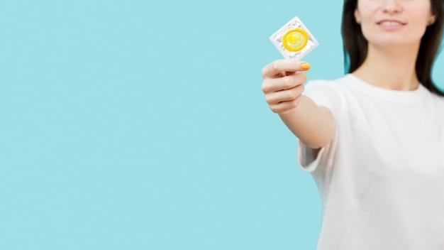 Mujer sosteniendo un condón amarillo con espacio de copia