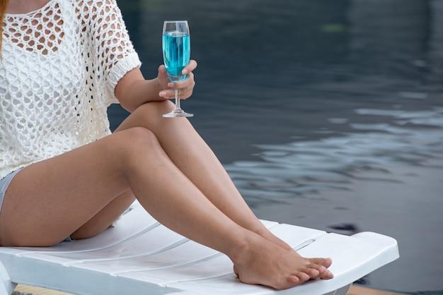 Mujer sosteniendo una copa de vino junto a la piscina