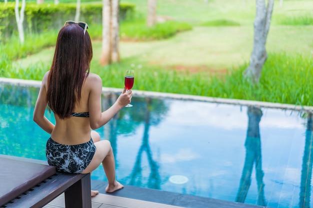 Mujer sosteniendo una copa de vino en la piscina