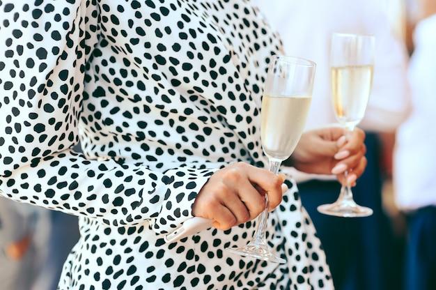Mujer sosteniendo copas con champagne