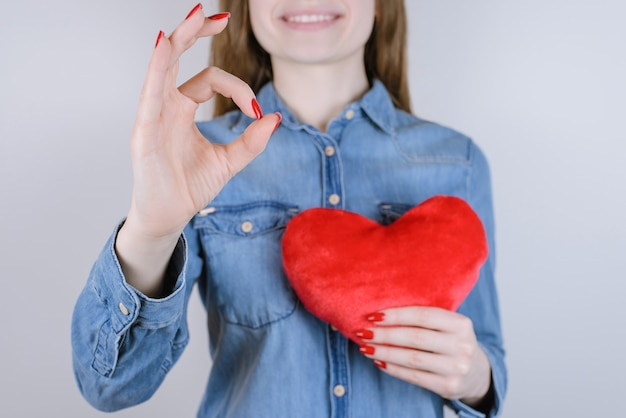 Mujer sosteniendo corazón rojo mostrando signo bien con los dedos