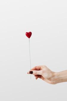 Mujer sosteniendo un corazón rojo en un palo