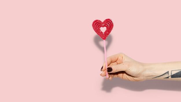 Mujer sosteniendo un corazón rojo en un papel tapiz de palo