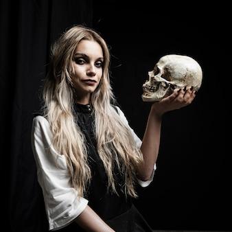 Mujer sosteniendo el cráneo con fondo negro