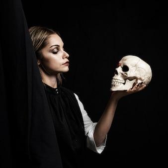 Mujer sosteniendo cráneo sobre fondo negro