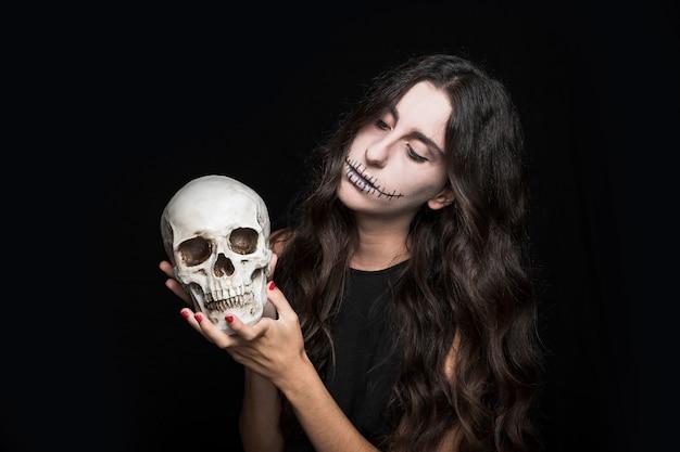 Mujer sosteniendo el cráneo