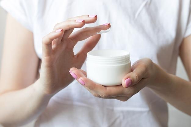 Mujer sosteniendo crema para manos y cuerpo en sus manos. foto de alta calidad