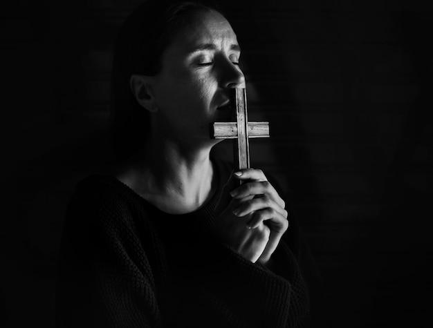 Mujer sosteniendo cruz orando por dios