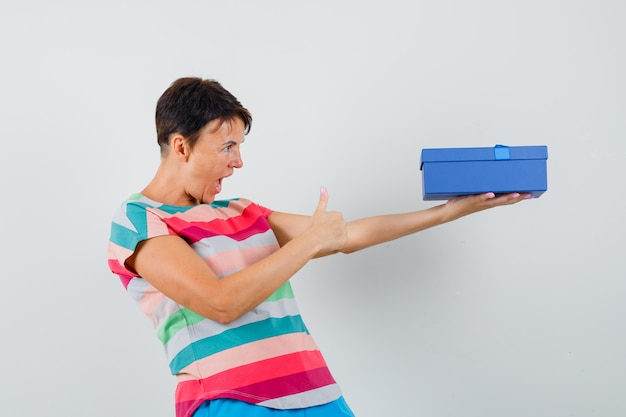 Mujer sosteniendo el cuadro actual, mostrando el pulgar hacia arriba en camiseta a rayas, pantalones y mirando feliz