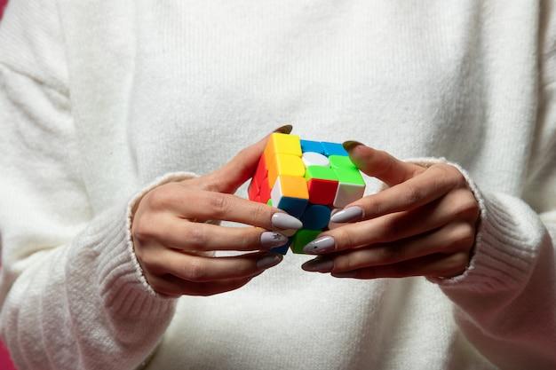 Mujer sosteniendo el cubo de rubik en manos
