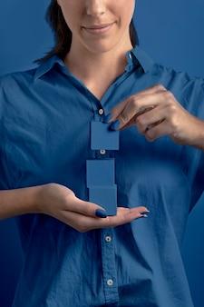 Mujer sosteniendo cubos apilados de color azul clásico