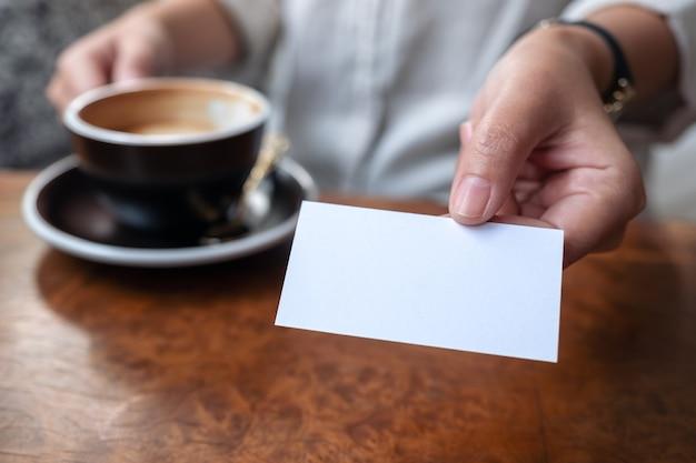 Una mujer sosteniendo y dando una tarjeta de presentación vacía en blanco a alguien mientras bebe café