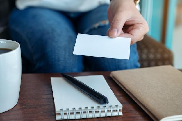 Una mujer sosteniendo y dando una tarjeta de presentación vacía en blanco a alguien