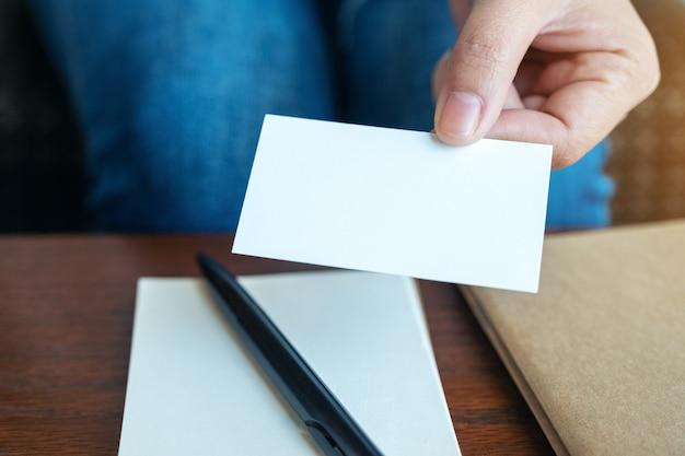 Una mujer sosteniendo y dando una tarjeta de visita vacía a alguien.
