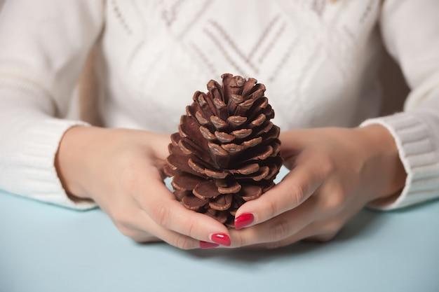 Mujer sosteniendo una decoración de navidad gran cono de pino en una mano en azul