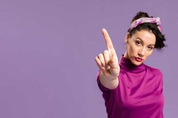 Mujer sosteniendo un dedo hacia arriba y copia espacio