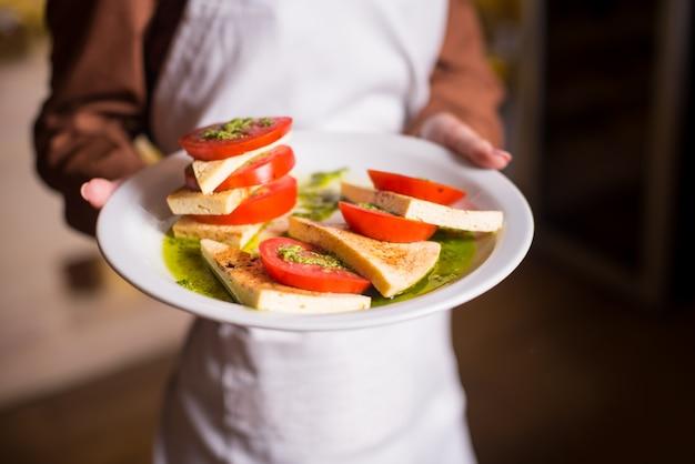 Mujer sosteniendo deliciosas comidas vegetarianas ensalada de tomate caprese