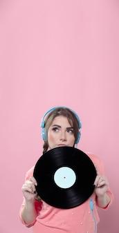 Mujer sosteniendo un disco de vinilo mientras usa auriculares