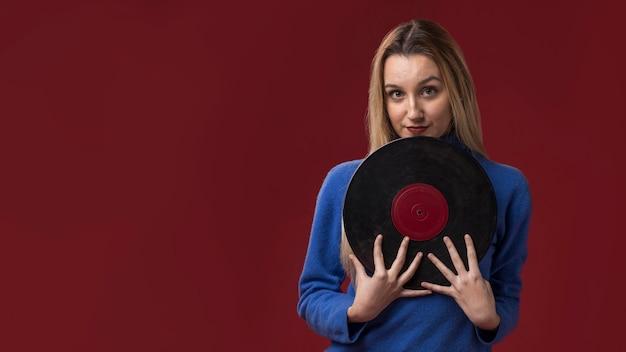 Mujer sosteniendo un disco de vinilo
