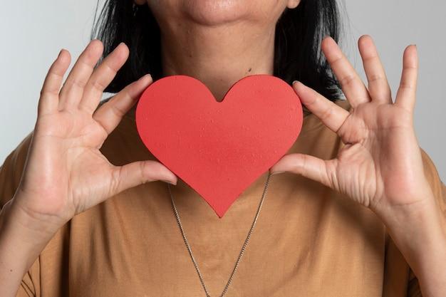 Mujer sosteniendo un diseño de corazón delante de su cuello