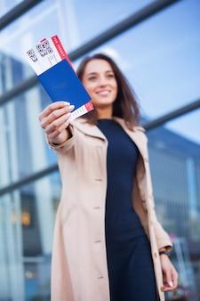 Mujer sosteniendo dos billetes de avión en el pasaporte en el extranjero cerca del aeropuerto
