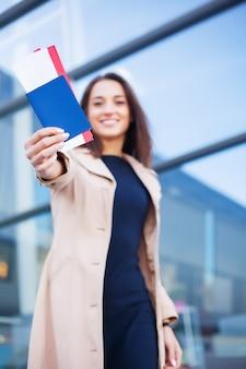 Mujer sosteniendo dos pasajes aéreos en el pasaporte extranjero cerca del aeropuerto
