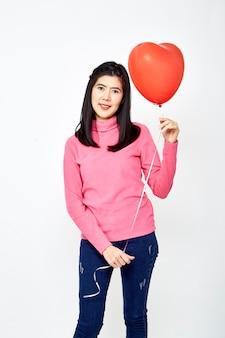 Mujer sosteniendo el globo en forma de corazón rojo