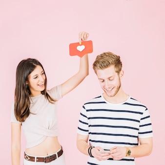 Mujer sosteniendo el icono de amor sobre la cabeza de su novio usando el teléfono móvil