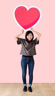 Mujer sosteniendo un emoticon de corazón en un estudio